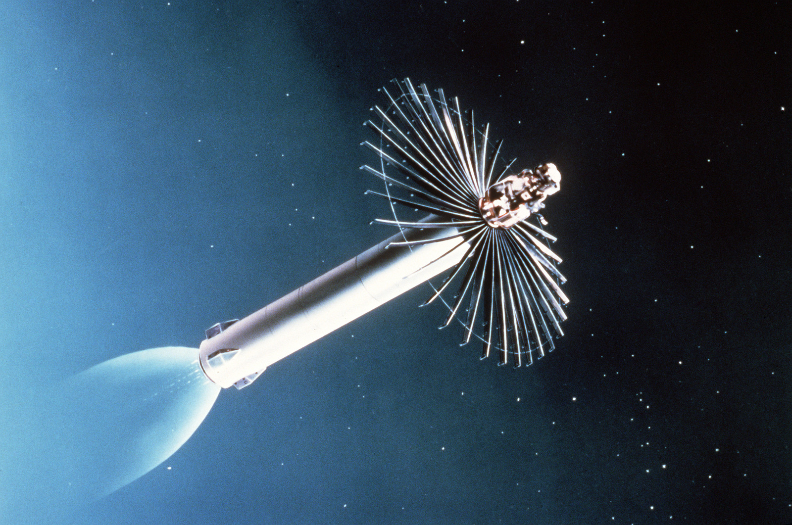"""An artist's concept of the Army Homing Overlay Experiment (HOE) homing and kill vehicle preparing to intercept a mock nuclear warhead more than 100 miles above the mid-Pacific Ocean. The HOE sensor in nose locks onto the target and the third stage axial propulsion motor maneuvers the vehicle onto a collision course. The 15-foot radial """"net"""" opens to destroy the incoming warhead by impact at more than 15,000 feet per second"""