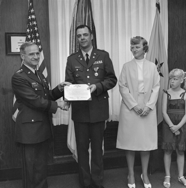 Lieutenant General (LGEN) Ernest D. Peixotto, Comptroller of the Army, presents the Legion of Merit to Colonel (COL) Patrick J. Cunningham. Present for the ceremony was COL Cunningham's wife Shela and daughter Catheren