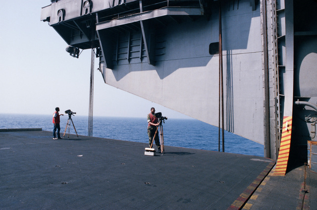A crew from the Naval Audiovisual Center shoots motion picture footage from the deck edge elevator aboard the aircraft carrier USS JOHN F. KENNEDY (CV 67)