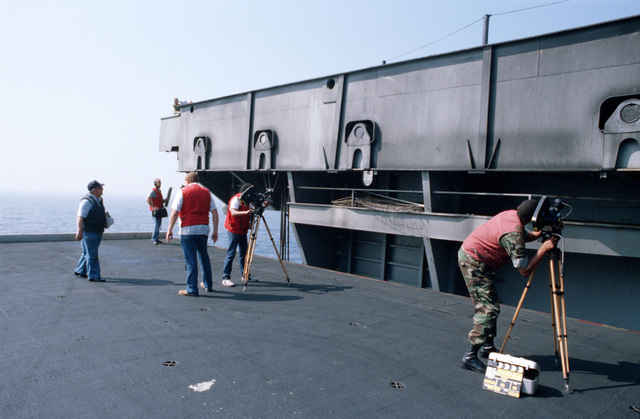 A crew from the Naval Audiovisual Center shoots motion picture footage on the deck edge elevator aboard the aircraft carrier USS JOHN F. KENNEDY (CV 67)