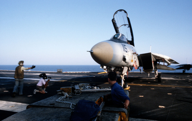 A motion picture shoot crew member from the Naval Audiovisual Center films an F-14A Tomcat aircraft being backed onto an elevator aboard the aircraft carrier USS JOHN F. KENNEDY (CV 67)