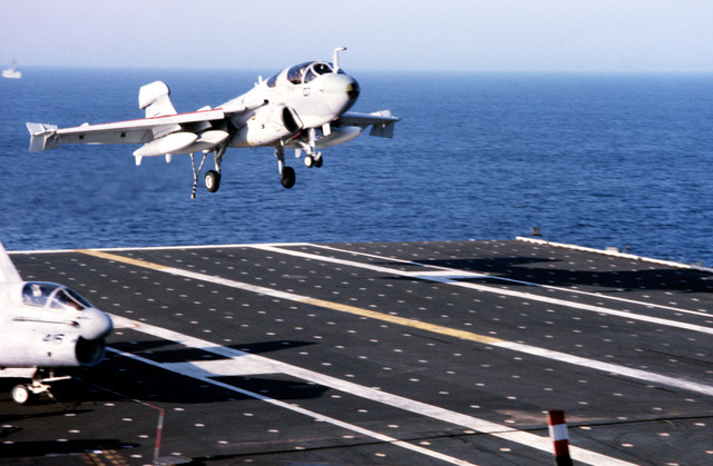 A right front view of an EA-6B Prowler aircraft landing on the flight deck of the aircraft carrier USS JOHN F. KENNEDY (CV 67). An A-7 Corsair II aircraft is parked to the left