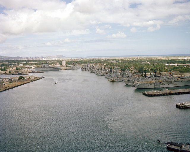 Aerial view of Pearl Harbor with the amphibious assault ship USS NEW ORLEANS (LPH 11) visible to the right. Also visible is the destroyer USS KINKAID (DD 965)