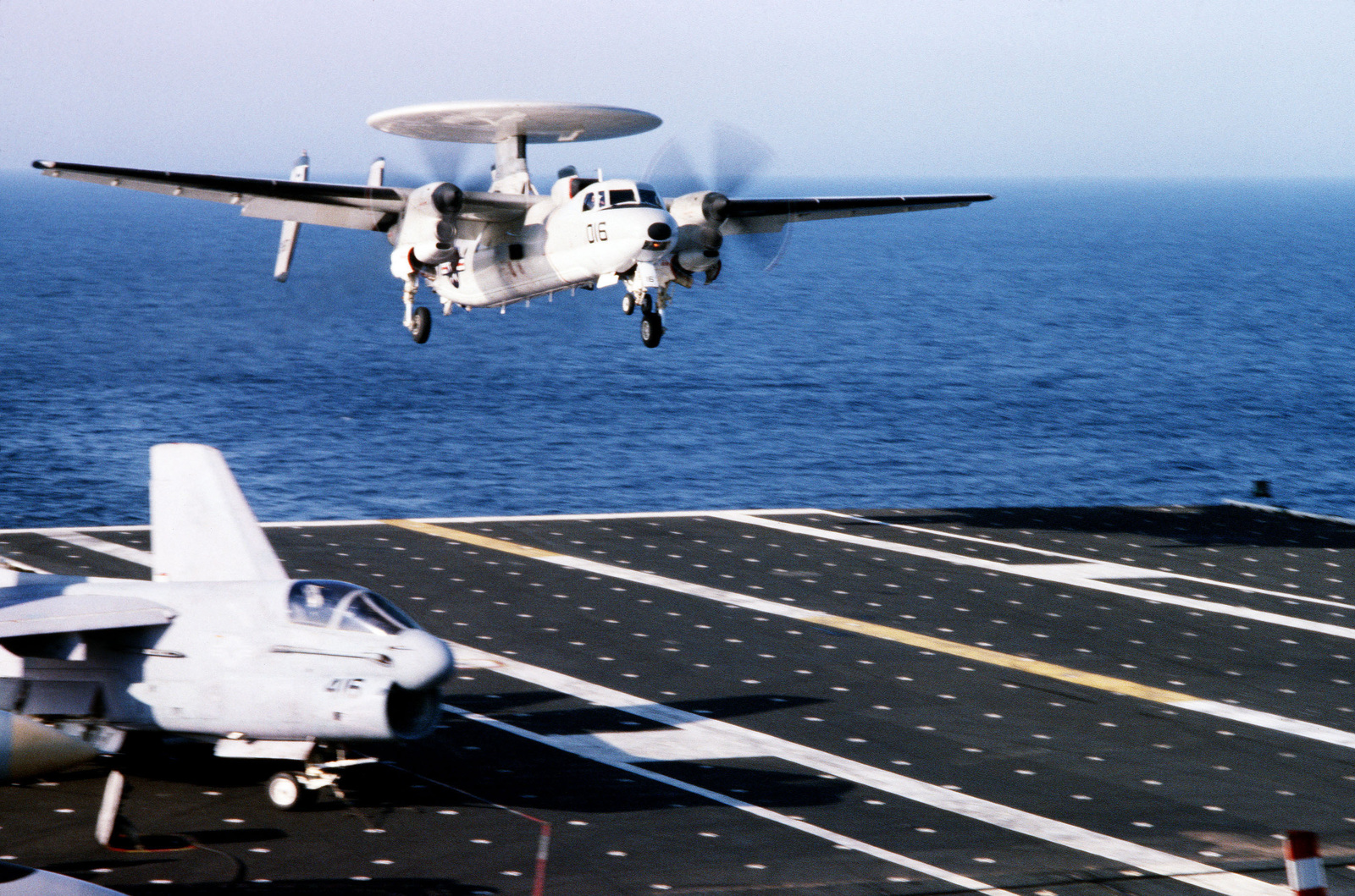 An E-2C Hawkeye airborne early warning aircraft comes in for a landing aboard the aircraft carrier USS JOHN F. KENNEDY (CV 67). An A-7 Corsair II aircraft are parked to the left