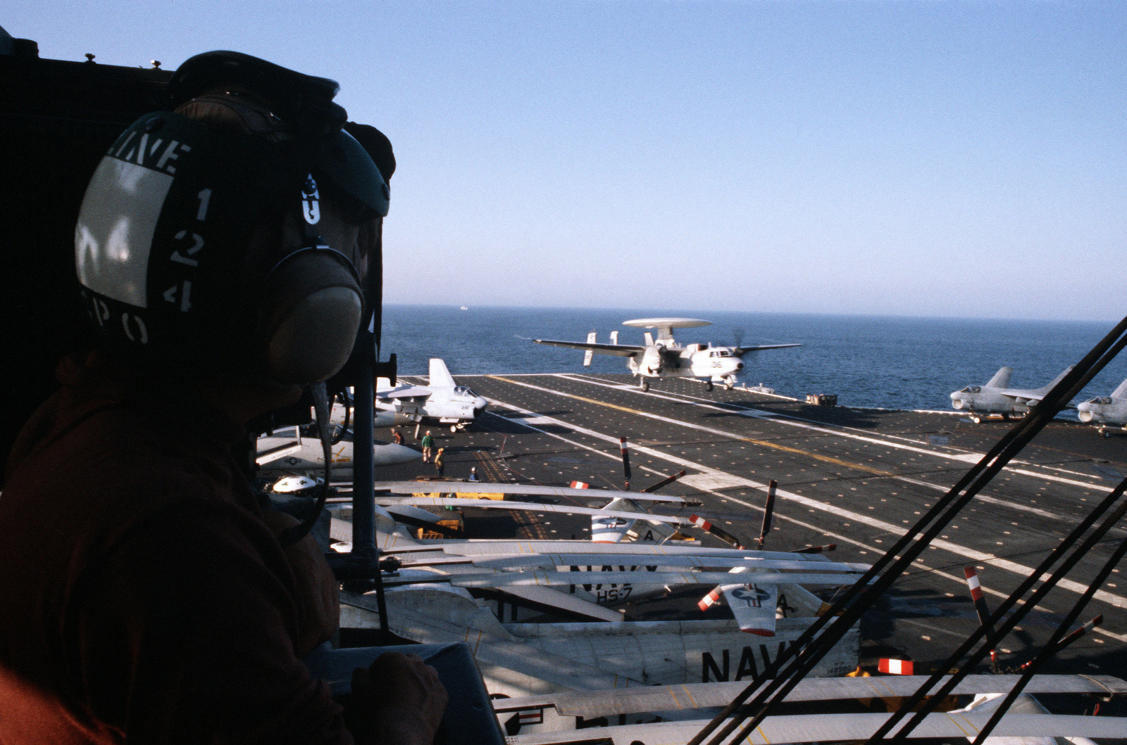 An E-2C Hawkeye airborne early warning aircraft comes in for a landing aboard the aircraft carrier USS JOHN F. KENNEDY (CV 67). A-7 Corsair II aircraft are parked on either side of the flight deck. An F-14A Tomcat aircraft and three SH-3 Sea King helicopters from Helicopter Anti-submarine Squadron (HS-7) are parked on the left