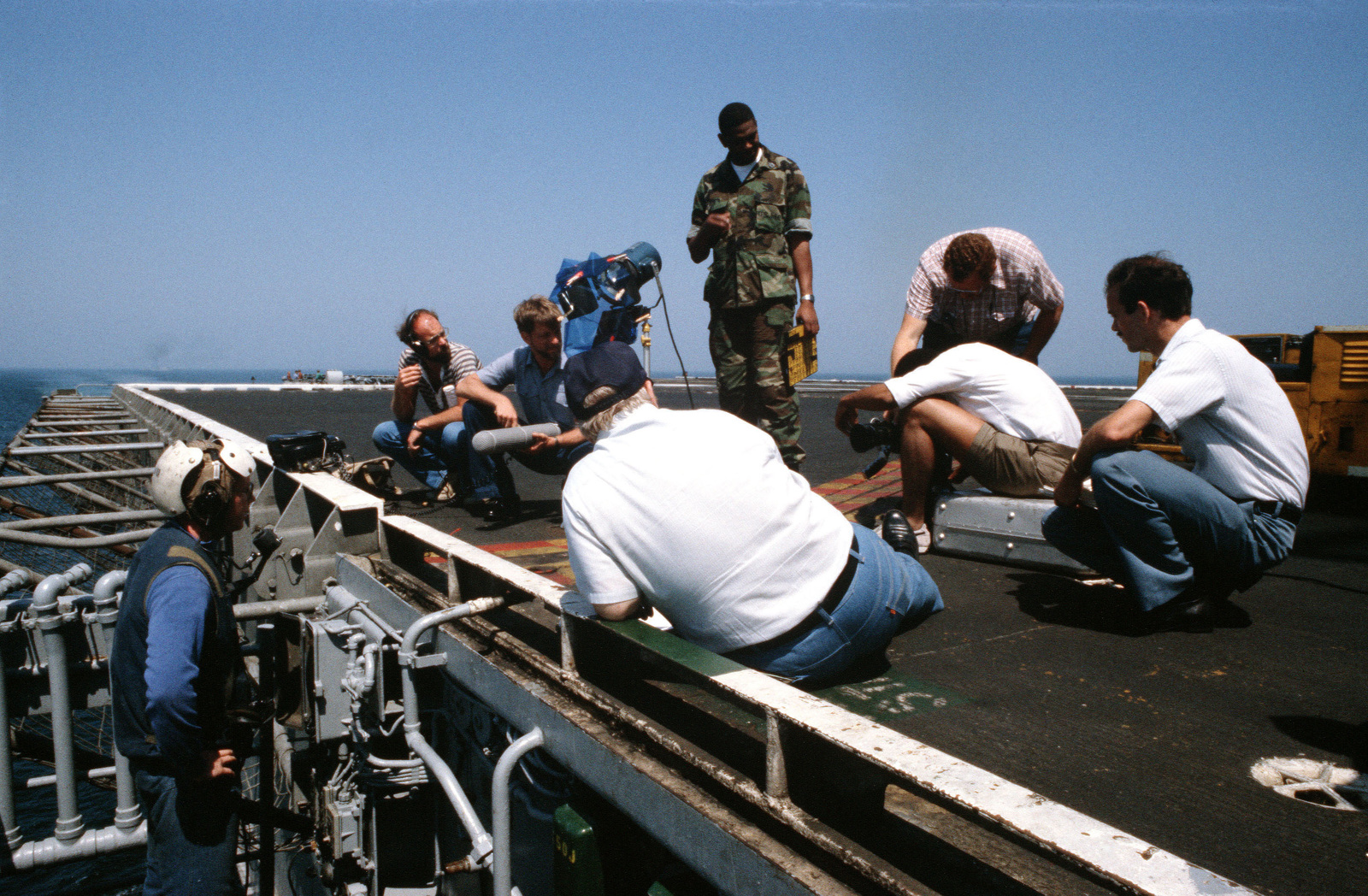 An elevator operator aboard the aircraft carrier USS JOHN F. KENNEDY (CV 67) watches as a motion picture crew from the Naval Audiovisual Center corrects a camera malfunction