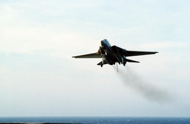 An F-14A Tomcat aircraft makes the final approach before landing aboard the aircraft carrier USS JOHN F. KENNEDY (CV 67)