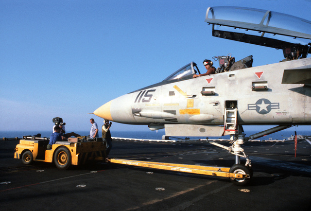An MD-3 tow tractor is used to move an F-14A Tomcat aircraft on the flight deck of the aircraft carrier USS JOHN F. KENNEDY (CV 67). A member of the Naval Audiovisual Center motion picture shoot crew is filming the operation