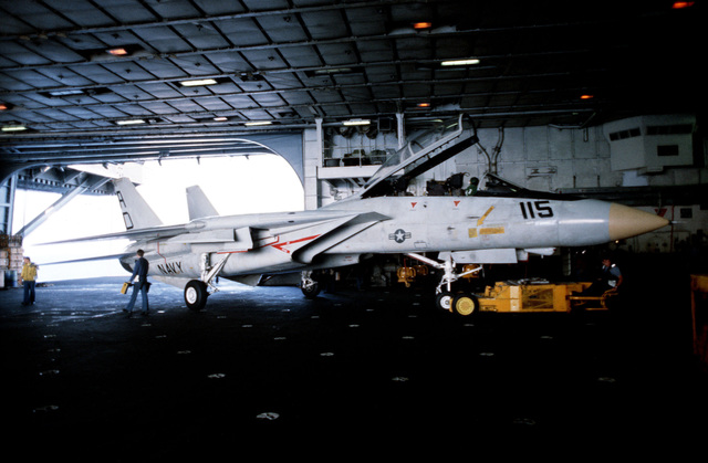 An SD-1D aircraft spotting dolly is used to move an F-14A Tomcat aircraft in hangar bay two aboard the aircraft carrier USS JOHN F. KENNEDY (CV 67)