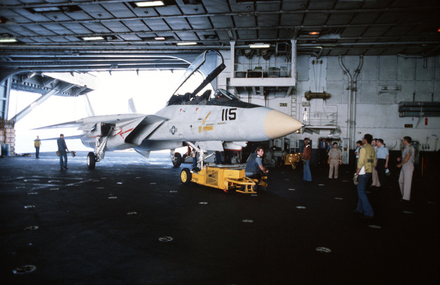 An SD-1D aircraft spotting dolly is used to move an F-14A Tomcat aircraft in hangar bay No. 2 aboard the aircraft carrier USS JOHN F. KENNEDY (CV 67)