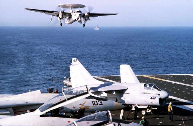 Left front view of an E-2C Hawkeye airborne early warning aircraft comes in for a landing aboard the aircraft carrier USS JOHN F. KENNEDY (CV 67). Two F-14A Tomcat aircraft and an A-7 Corsair II aircraft, right, are on the deck in the foreground