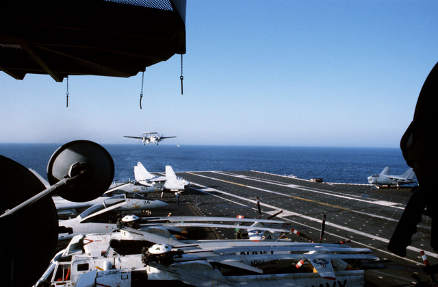 Pilot Landing Aid Television (PLAT), on the island camera station, foreground, is used to record an E-2C Hawkeye airborne early warning aircraft landing aboard the aircraft carrier USS JOHN F. KENNEDY (CV 67). A-7 Corsair II aircraft are parked on either side of the deck