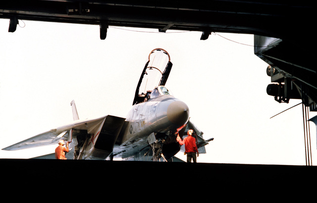 Right front view of an F-14A Tomcat aircraft on an elevator aboard the aircraft carrier USS JOHN F. KENNEDY (CV 67)