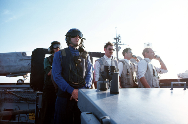 The landing signal officer directs an incoming plane as observers watch from the landing signal officer's platform aboard the aircraft carrier USS JOHN F. KENNEDY (CV 67)