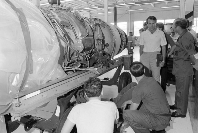 Congressman James A. Courter (Republican-New Jersey) (center) is briefed by Technical Sergeant Barry Shutts, (right) jet engine intermediate maintenance shop chief, on the maintenance procedures of the B-52 aircraft engine