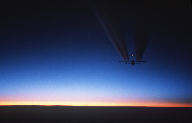 Rear view of a C-141B Starlifter aircraft, with contrails, flying toward the setting sun. The aircraft is returning to Christchurch, New Zealand, after a successful airdrop over Antarctica