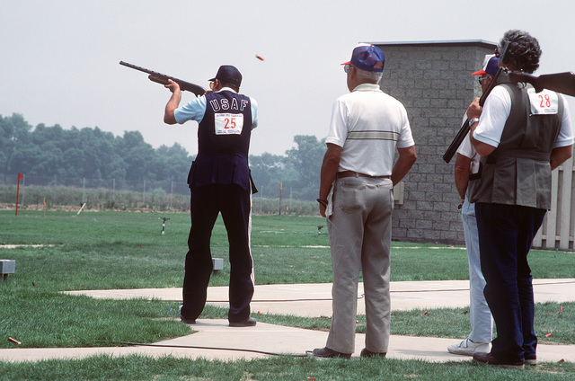 MASTER Sergeant (MSGT) Walter E. Eaddy, left, US Air Force Hospital, Williams Air Force Base, Arizona, competes as a member of the Air Force shooting team in the qualifications for the 1984 23rd Summer Olympics Shooting Team. He is firing a 12 gauge shotgun in the skeet clay target shooting event at the Olympic Shooting Venue. His skills are being observed by two referees, center, and another competitor