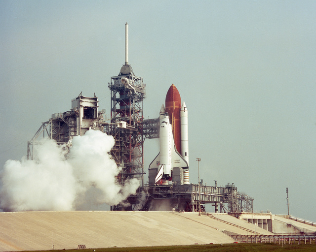 Space Shuttle Orbiter Discovery (OV-103) scheduled to lift off at 8:43 a.m. on mission 41-D, waits on the launch pad for the countdown to resume. The ignition sequence was halted at T minus four seconds by onboard computers when the No. 3 engine failed to achieve internal ignition