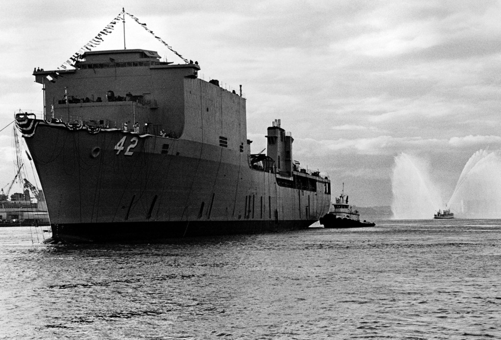 A port bow view of the dock landing ship USS GERMANTOWN (LSD 42) in the Duwamish River after its launching ceremony. One tug comes alongside at the stern while another sprays fountains of water to celebrate the launch