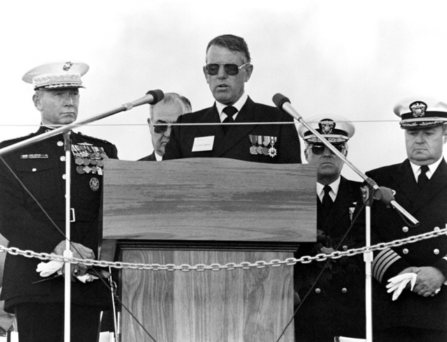 CAPT. Joseph F. Brennan, CHC, USN Command Chaplain, Naval Base Seattle, delivers the invocation during the launching ceremony for the dock landing ship GERMANTOWN (LSD-42). Behind him are, from left to right; GEN. P. D. Kelley, Commandant of the Marine Corps; Clarence E. Briggs, Pacific Coast Metal Trades; Commodore Bruce R. Boland; and Capt. Charles H. Piersall Jr