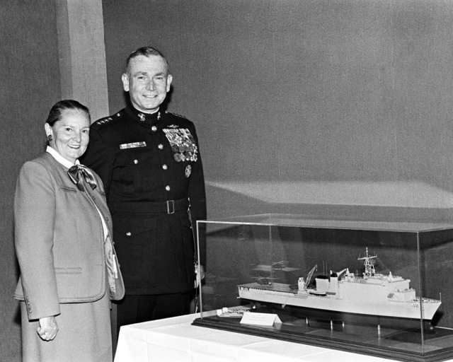 General P. X. Kelley, Commandant of the Marine Corps, sponsor, and his wife, Barbara, sponsor of the dock landing ship USS GERMANTOWN (LSD 42), during the ship's launching ceremony. They are posing beside a model of the GERMANTOWN