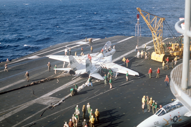 An NP-50 crane is moved into position to remove a damaged F-14A Tomcat aircraft from the flight deck after an emergency barricade landing aboard the aircraft carrier USS KITTY HAWK (CV 63). No injuries were sustained during the landing