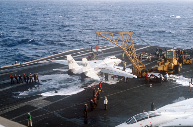 Crew members use an NP-50 crane to remove a damaged F-14A Tomcat aircraft from the flight deck after an emergency barricade landing aboard the aircraft carrier USS KITTY HAWK (CV 63). No injuries were sustained during the landing