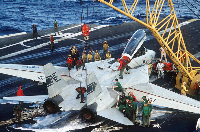 Crew members use an NP-50 crane to remove a damaged F-14A Tomcat aircraft from the flight deck after an emergency barricade landing aboard the aircraft carrier USS KITTY HAWK (CV-63). No injuries were sustained during the landing