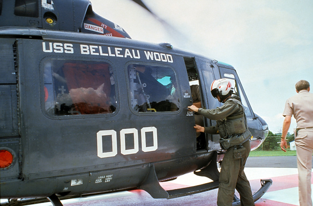 A Navy pilot closes the door of a UH-1 Iroquois helicopter carrying crash victim Lieutenant Junior Grade Eric Patenkopf to the regional medical center at Clark Air Base, Philippines. Patenkopf was rescued from the South China Sea after his A-4 Skyhawk aircraft developed engine problems, forcing him to eject