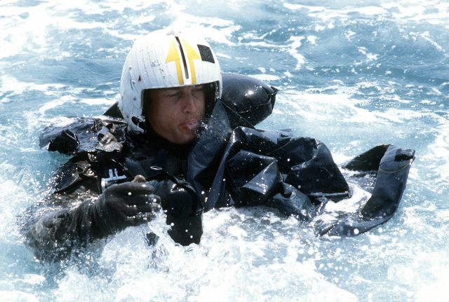 A student of Deep Water Environmental Survival Training (DWEST) struggles to inflate an LR-1 life raft as part of the training course. All Hands Magazine - July 1984