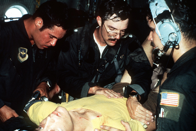 AIRMAN 1ST Class Daniel Volz, right, takes a blood pressure reading as LCDR Matthew Waack, center, checks crash victim LTJG Eric Patenkopf for abdominal injuries. Patenkopf was rescued from the South China Sea after his A-4 Skyhawk aircraft developed engine problems, forcing him to eject. Exact Date Shot Unknown
