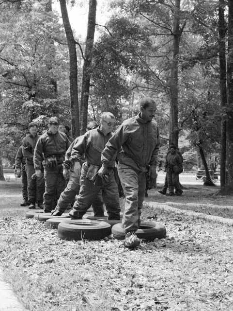 Airmen wearing nuclear-biological-chemical (NBC) protective suits participate in obstacle course training during an NBC warfare exercise