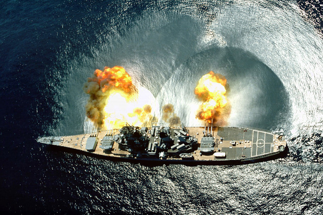 An overhead view of the battleship USS IOWA (BB-61) firing all 15 of its guns (nine 16-inch and six 5-inch) during a target exercise near Vieques Island. Careful observation of the three main turrets shows the barrels in various states of recoil