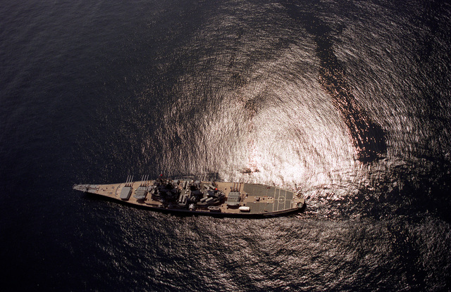 An overhead view of the battleship USS IOWA (BB-61) with its guns trained to fire a broadside to starboard