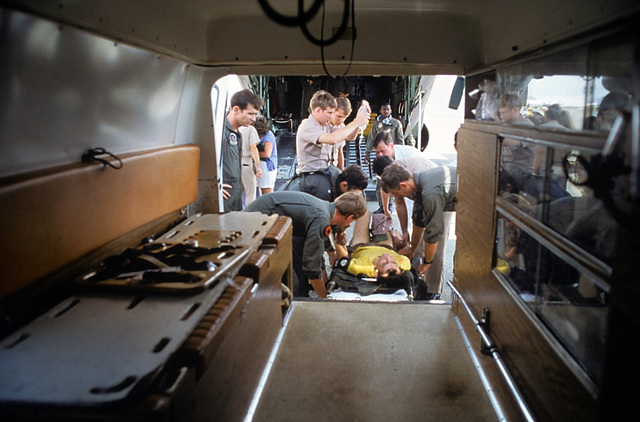 Crash victim Lieutenant Junior Grade Eric Patenkopf is transferred from a C-130 Hercules aircraft to an ambulance enroute to an emergency room at the station's hospital facility. Patenkopf was rescued from the South China Sea after his A-4 Skyhawk developed engine problems, forcing him to eject