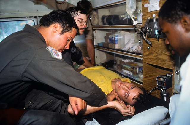 Crash victim Lieutenant Junior Grade Eric Patenkopf is transported by ambulance to the emergency room at the station's hospital facilities. He is attended by AIRMAN First Class Daniel Volz, left. Patenkopf was rescued from the South China Sea after his A-4 Skyhawk aircraft developed engine problems, forcing him to eject
