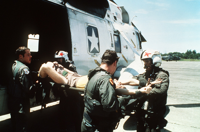 Crash victim LT. j.g. Eric Patenkopf is transferred from an SH-3 Sea King helicopter to a C-130 Hercules aircraft from the 21st Tactical Airlift Squadron for medical evacuation at Cubi Point Naval Air Station, Philippines. Patenkopf was rescued from the South China Sea after his A-4 Skyhawk aircraft developed engine problems, forcing him to eject