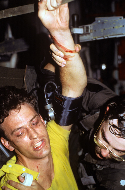 Lieutenant Commander Matthew Waack, restrains crash victim Lieutenant Junior Grade Eric Patenkopf while his vital signs are taken. Patenkopf was rescued after his A-4 Skyhawk aircraft developed engine problems, forcing him to eject