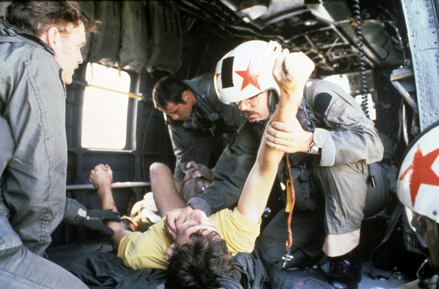 US Navy and US Air Force rescue personnel administer first-aid to Lieutenant Junior Grade Eric Patenkopf aboard an SH-3 Sea King helicopter. Patenkopf was rescued after his A-4 Skyhawk developed engine problems forcing him to eject
