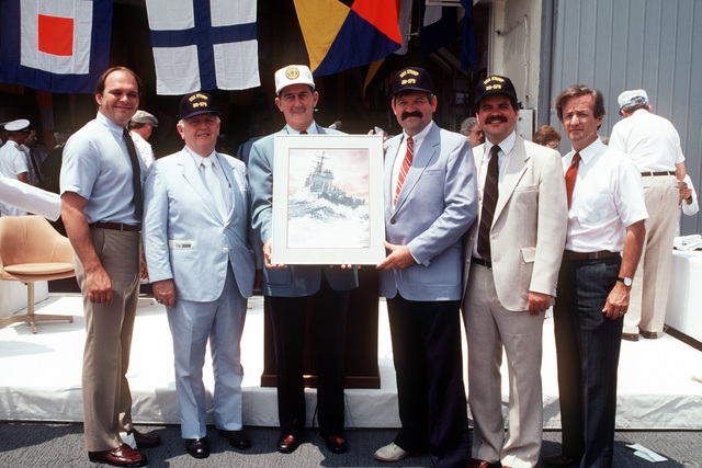 Members of the West Virginia state legislature pose with a painting of the USS STUMP (DD 978) during a ceremony aboard the destroyer as the flagship for their state. The ship is underway near Norfolk, Virginia