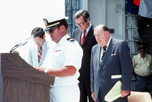Sen. Jennings Randolph (D-W.Va.), right, West Virginia Gov. John D. Rockefeller IV, background, and Congressman Alan B. Mollohan (D-W.Va.) stand behind a Navy chaplain as he delivers an invocation during a ceremony to adopt the destroyer USS STUMP (DD-978) as flagship for the state of West Virginia. The ship is underway near Norfolk, Va