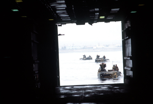 Three AAVP-7 amphibious assault vehicles approach the open stern gate of the tank landing ship USS FAIRFAX COUNTY (LST-1193) off the coast near Naval Station, Roosevelt Roads, Puerto Rico, during UNITAS XXV, an Exercise involving forces from the US and six South American nations