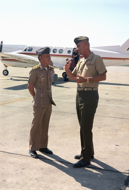 Major General Robert Haebel, commanding general, Camp Pendleton, says farewell to Philippine General Rodolfo Punsalang after his tour of the base. A UC-12B Huron aircraft is parked in the background