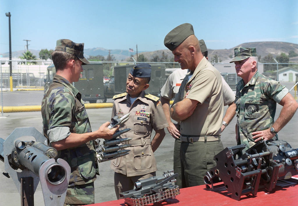 Sergeant Charles Varga of the Instructural Section, S-3, Infantry Training School, explains the operation of the 25 mm cannon of an LAV25 light armored vehicle to Philippine General Rodolfo Punsalang, center, and Major General Robert Haebel, commanding general, Camp Pendleton