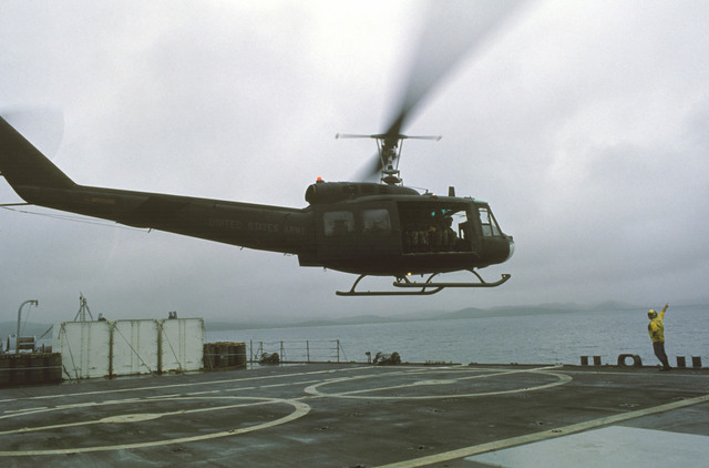 An Army UH-1 Iroquois helicopter lifts off from the deck of the tank landing ship USS FAIRFAX COUNTY (LST 1193) during Exercise FUERZAS UNIDAS. It is transporting Ecudadorian soldiers to Valdivia Beach for a beach assault