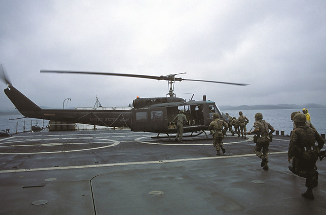 Right side view of a UH-1 Iroquois helicopter aboard the tank landing ship USS FAIRFAX COUNTY (LST 1193) as Ecuadorian soldiers approach to go aboard at the beginning of Exercise FUERZAS UNIDAS