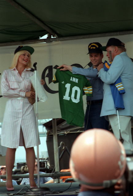 A sailor presents a Forrestal jersey to actress Ann Jillian during a 30-minute show with Bob Hope on board the aircraft carrier USS FORRESTAL (CV 59)