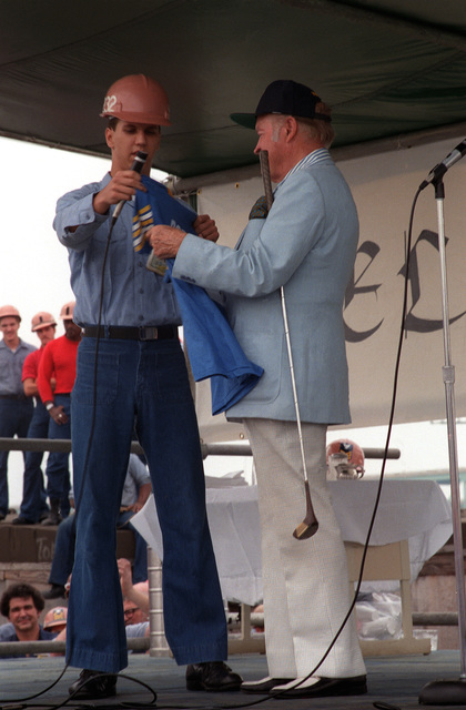 A sailor presents a FORRESTAL jersey to Bob hope during the entertainer's 30-minute show on board the aircraft carrier USS FORRESTAL (CV-59)
