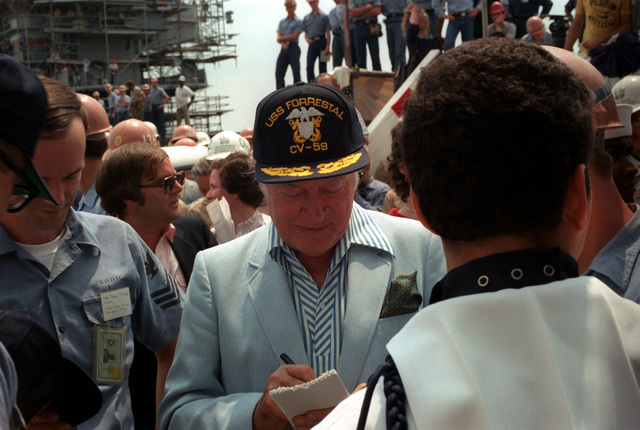 Bob Hope signs autograph after a 30-minute show with actress Ann Jillian on board the aircraft carrier USS FORRESTAL (CV 59)