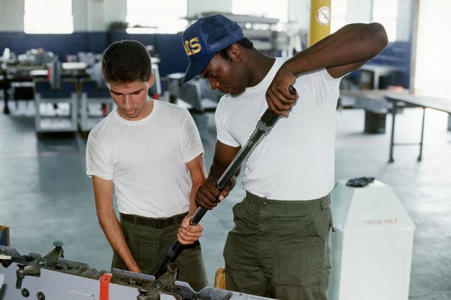 AIRMAN First Class (A1C) Robert J. Sullivan (left) and AIRMAN First Class (A1C) Patrick C. Thornton, 56th Munitions Maintenance Squadron, install a bomb rack in a centerline pylon